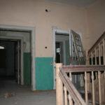 Klatka schodowa przed remontem. Na ścianach kondygnacji widoczne stare powłoki malarskie, zielone lamperie.