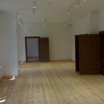 Największe pomieszczenie na parterze budynku numer 1 po wykonanym remoncie, jeszcze bez jakiegokolwiek wyposażenia. Zachowana historyczna stolarka pomalowana na kolor ciemnobrązowy. Jasne, sosnowe podłogi.