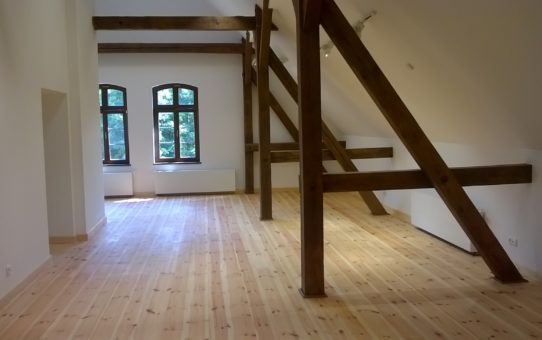 Poddasze muzeum po remoncie z częściowo widoczną więźbą dachową w ciemnym, brązowym kolorze. Podłoga jasna, sosnowa.