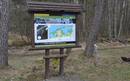 """Tablica edukacyjna na drewnianym stelażu z daszkiem. U góry tytuł Ścieżka przyrodnicza """"Światło Latarni"""". Po lewej stronie mapa przebiegu ścieżki. Po prawej mapa SPN z lokalizacją infrastruktury edukacyjnej."""
