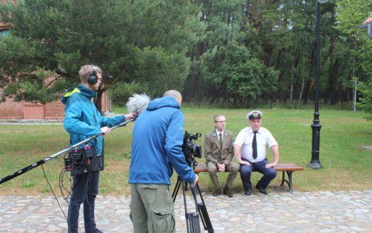 Na pierwszym planie ekipa filmowa na terenie Osady Latarników w Czołpinie. Realizator dźwięku z mikrofonem na wysięgniku oraz operator z kamerą na stojaku. Dwóch aktorów siedzących na ławce. Mężczyzna z lewej w mundurze pracownika Parku Narodowego. Drugi w mundurze latarnika.