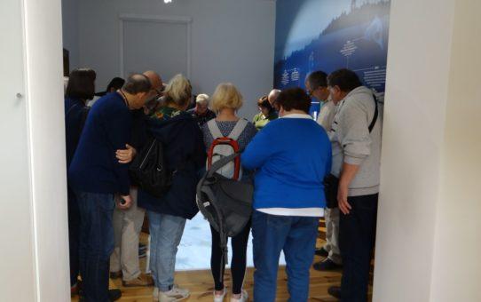 W sali muzealnej widzimy plecy kobiet i mężczyzn z zainteresowaniem oglądających wystawę.