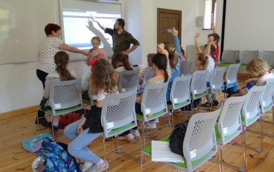 Przed aktywną tablicą multimedialną na krzesłach siedzą uczniowie. Pracownik edukacyjny Parku i nauczyciel stoją przed tablicą. Część uczniów zgłasza się do odpowiedzi podnosząc dłonie do góry.