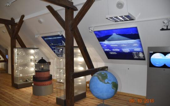 Widok ekspozycji na poddaszu muzeum. Przestrzeń dzielą drewniane legary, a pomiędzy nimi globus, szklane gabloty i plansze edukacyjne.