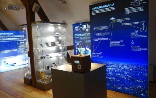 Sala wystawowa muzeum latarnictwa. Na pierwszym planie urządzenie do radionawigacji. W głębi gablota wystawiennicza i tablice tematyczne.
