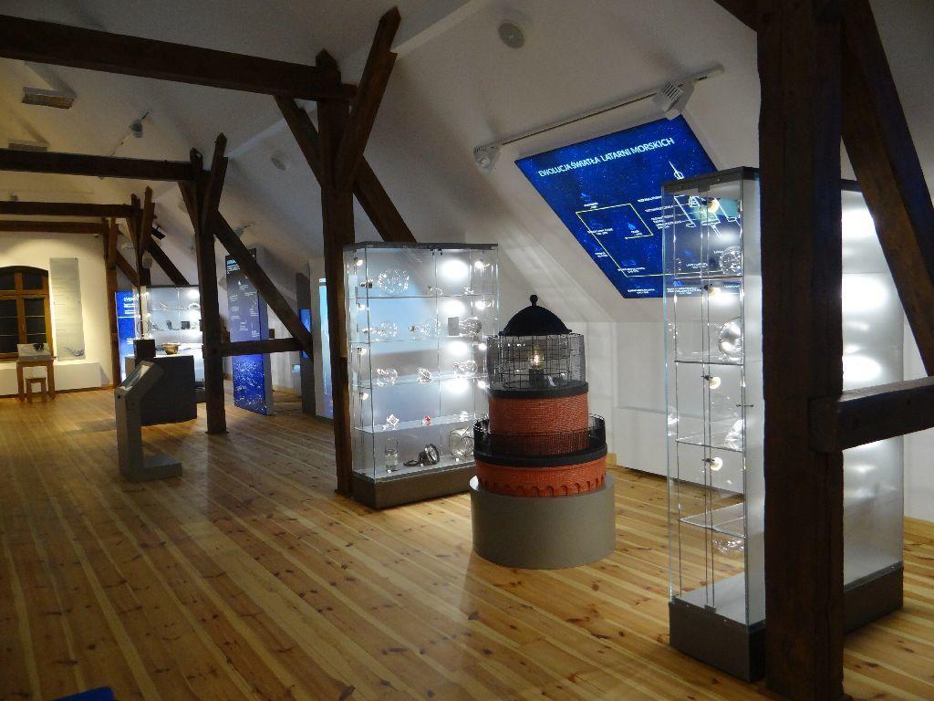 Sala ekspozycyjna Muzeum Latarnictwa. Pomiędzy przeszklonymi, podświetlanymi gablotami zeksponatami stoi miniatura szczytowej części latarni morskiej.