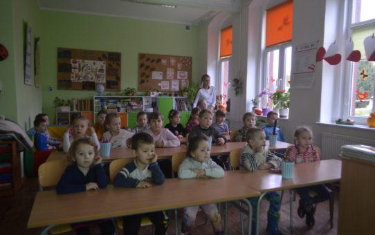 W klasie lekcyjnej w trzech rzędach ławek siedzą dzieci klas I-III uczestniczące w zajęciach. Z prawej strony pod oknem stoi nauczyciel.