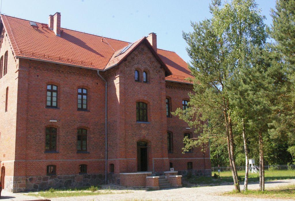 Dwukondygnacyjny budynek zczerwonej cegły pokryty dachówką. Nawprost głównego wejścia dobudynku rośnie kępa brzóz.