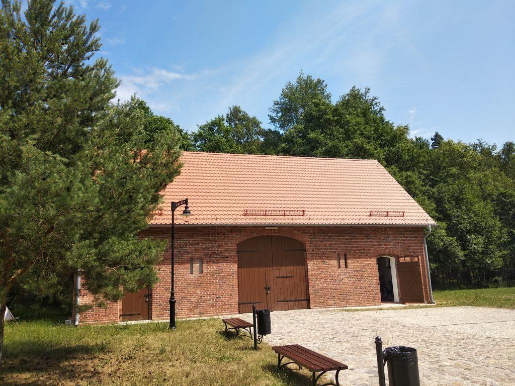 Do budynku dawnej stodoły zbudowanej zczerwonej cegły prowadzi brukowana droga przy którejstoją ławeczki. Budynek otoczony drzewami.