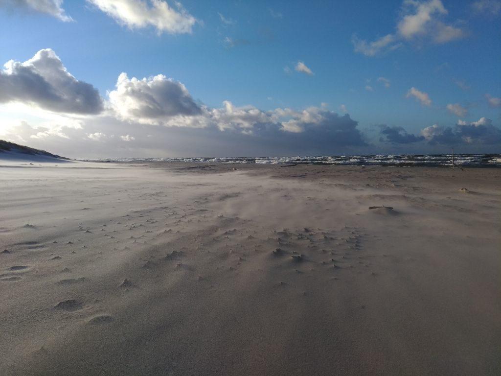W pogodny, jesienny dzień, kilka centymetrów nadplażą, widoczna jest delikatna mgiełka. Todrobne ziarenka piasku, poderwane zplaży podwpływem wiatru.