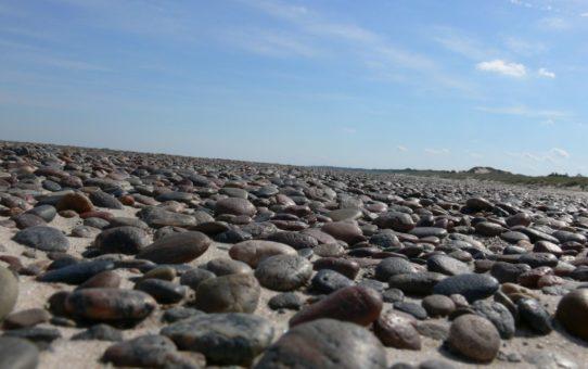 Na zdjęciu wykonanym z poziomu gruntu widać szeroką plażę w całości usłaną otoczakami, które w tym ujęciu wydają się bardzo duże. W tle widać błękitne niebo z białymi chmurkami.
