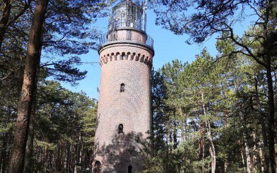 Okrągła, ceglana wieża latarni morskiej w Czołpinie zwieńczona galerią widokową i laterną