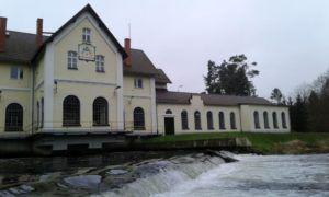 Elektrownia wodna w Żelkowie widoczna od frontu oraz bystry strumień wodny płynący przed nią.