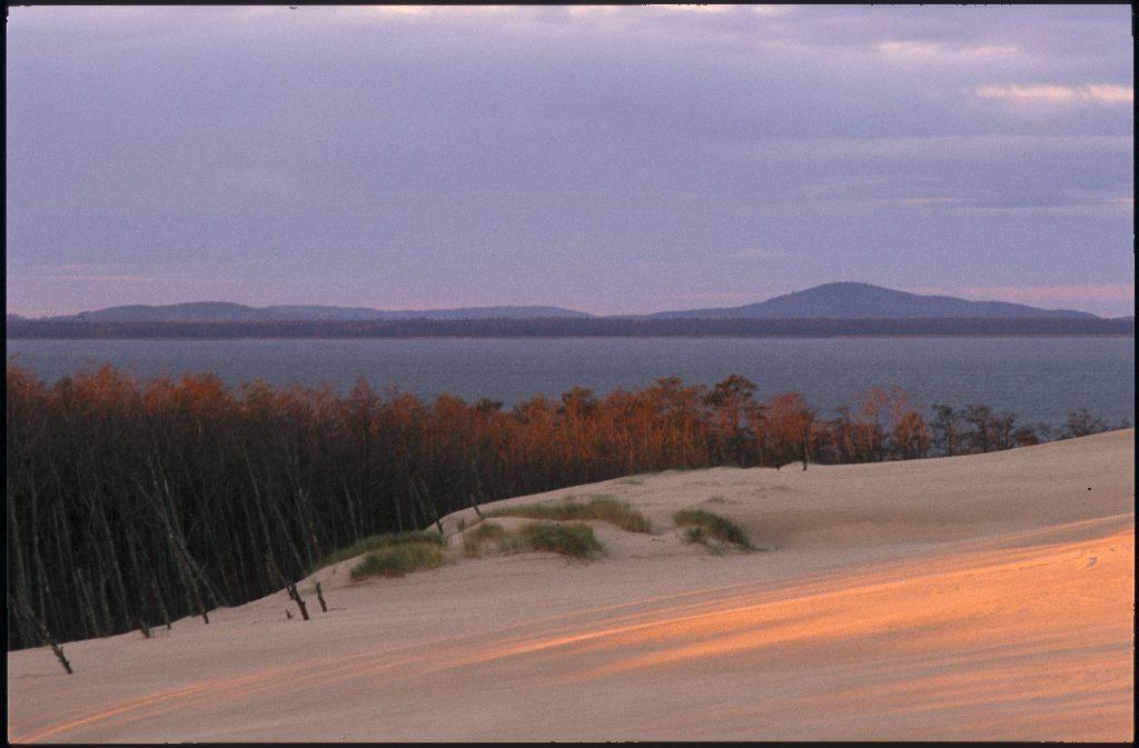 Pod stopami fotografa wydmy ruchome, znimi gładka tafla jeziora Łebsko, anahoryzoncie poprawej stronie widać wyraźny stożek Rowokołu.