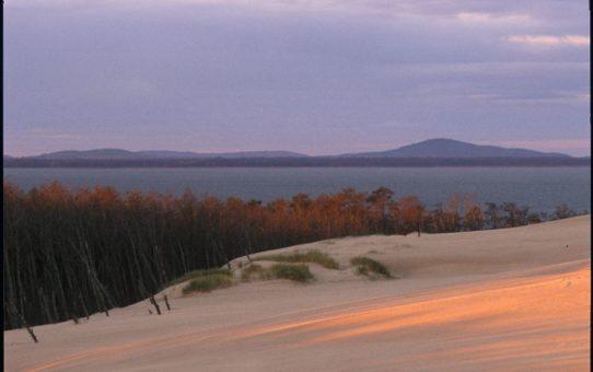 Pod stopami fotografa wydmy ruchome, z nimi gładka tafla jeziora Łebsko, a na horyzoncie po prawej stronie widać wyraźny stożek Rowokołu.
