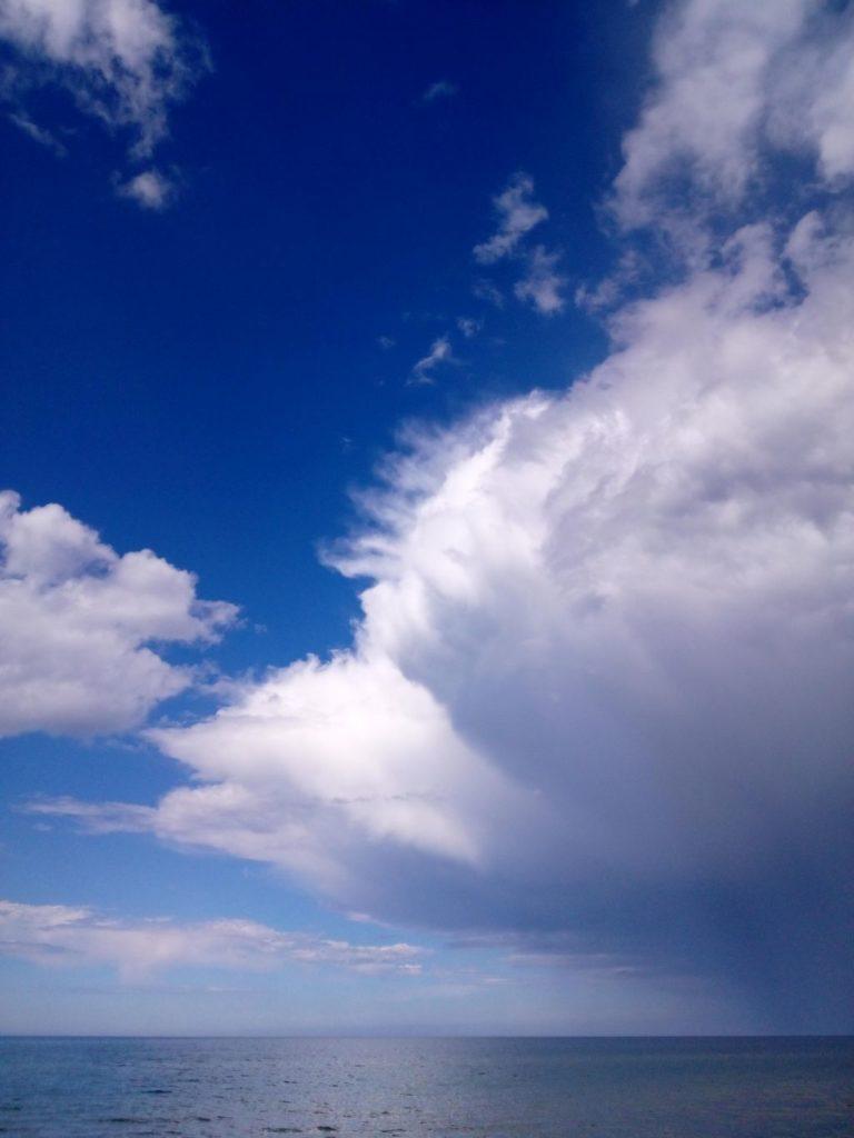 Widok namorze. Krajobraz naturalny wpostaci wody orazolbrzymiej chmury deszczowej obejmującej połowę kadru.