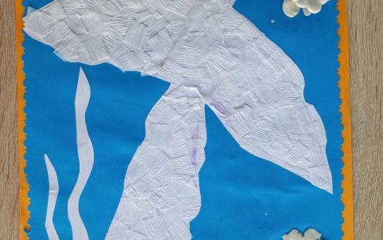 Praca plastyczna przedstawiajaca mewę srebrzystą. Na błękitnym tle znajduje się kontur ptaka wycięty z papieru i oklejony białą bibułą. Całość dopełniają trzy okrągłe obłoczki z plasteliny.